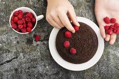 Gâteau fait maison fou de chocolat décoré des framboises par les mains masculines sur un fond gris Vue supérieure Photo libre de droits