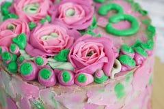 Gâteau magnifique couvert dans les roses faites de glaçage de crème de beurre sur le fond en bois blanc Photos libres de droits