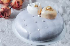 Gâteau mousseline couvert de lustre de miroir Décoré de deux coeurs blancs de chocolat Sur un fond blanc à côté du gâteau soyez photo stock