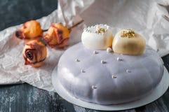 Gâteau mousseline couvert de lustre de miroir Décoré de deux coeurs blancs de chocolat Sur un fond en bois à côté du gâteau soyez images stock