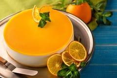 Gâteau orange dans le plat blanc sur la table en bois bleue Images libres de droits