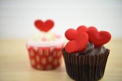 Gâteau romantique de tasse de chocolat de jour de valentines avec les décorations rouges de coeur d'amour sur le dessus Images stock