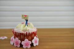 Gâteau romantique de tasse dans rose et blanc avec la figurine miniature de personne sur le dessus tenant un panneau de signe Photos libres de droits