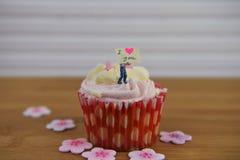 Gâteau romantique de tasse dans rose et blanc avec une figurine miniature de personne tenant un panneau de signe sur le dessus Image libre de droits