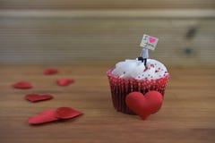 Gâteau romantique de tasse en rouge et blanc avec une figurine miniature de personne tenant un panneau de signe sur le dessus et  Photographie stock libre de droits