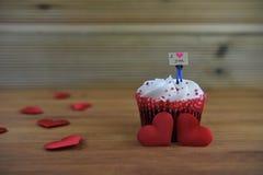 Gâteau romantique de tasse en rouge et blanc avec une figurine miniature de personne tenant un panneau de signe sur le dessus et  Images libres de droits