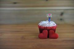 Gâteau romantique de tasse en rouge et blanc avec une figurine miniature de personne tenant un panneau de signe sur le dessus et  Photos stock
