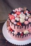 Gâteau rose rustique avec des baies, des guimauves et des macarons sur le dessus Photo stock