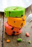Gâteau roulé lumineux de couleur différente sur la table en bois Image stock