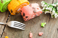 Gâteau roulé lumineux de couleur différente sur la table en bois Image libre de droits