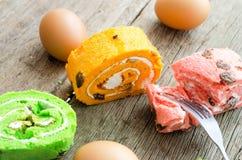 Gâteau roulé lumineux de couleur différente sur la table en bois Photographie stock libre de droits