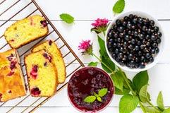 Gâteau savoureux sensible de lait caillé avec le cassis, les baies mûres et la confiture sur un fond en bois blanc Image libre de droits