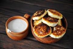 Gâteaux au fromage avec la crème sure en poterie sur une table en bois photos stock