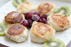 Gâteaux au fromage avec le kiwi et les canneberges Photographie stock
