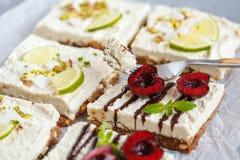 Gâteaux au fromage crus de pistache, de noix de coco, de chaux et de chocolat-cerise Photo libre de droits