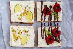 Gâteaux au fromage crus de pistache, de noix de coco, de chaux et de chocolat-cerise Photographie stock libre de droits