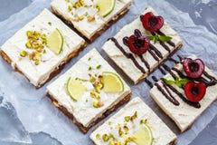Gâteaux au fromage crus de pistache, de noix de coco, de chaux et de chocolat-cerise Images libres de droits