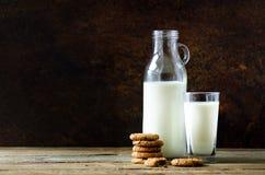 Gâteaux aux pépites de chocolat, bouteille et verre de lait sur la table en bois, fond foncé Matin ensoleillé, l'espace de copie Images stock