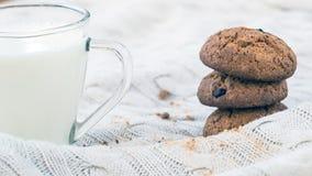 Gâteaux aux pépites de chocolat de farine d'avoine et un verre de lait sur un fond beige tricoté Festins de Noël Sélectif peu pro photos libres de droits