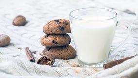 Gâteaux aux pépites de chocolat de farine d'avoine et un verre de lait sur un fond beige tricoté Festins de Noël Sélectif peu pro photographie stock libre de droits