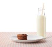Gâteaux aux pépites de chocolat du plat et de la bouteille blancs de lait Photo libre de droits