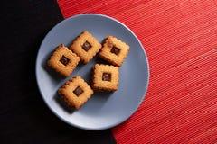 Gâteaux aux pépites de chocolat empilés de plat gris de style sur la table en bois rouge et noire Photo libre de droits