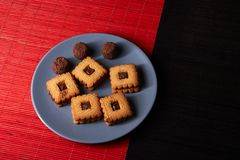 Gâteaux aux pépites de chocolat empilés de plat gris de style sur la table en bois rouge et noire Images stock