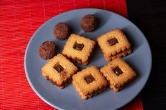 Gâteaux aux pépites de chocolat empilés de plat gris de style sur la table en bois rouge et noire Photographie stock libre de droits