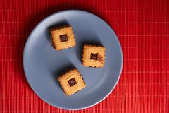 Gâteaux aux pépites de chocolat empilés de plat gris de style sur la table rouge Photographie stock