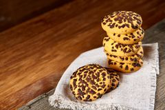 Gâteaux aux pépites de chocolat empilés sur la serviette de fabrication domestique blanche dans le style campagnard, foyer sélect Photo libre de droits