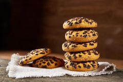 Gâteaux aux pépites de chocolat empilés sur la serviette de fabrication domestique blanche dans le style campagnard, foyer sélect Photographie stock libre de droits