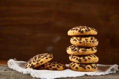 Gâteaux aux pépites de chocolat empilés sur la serviette de fabrication domestique blanche dans le style campagnard, foyer sélect Photo stock