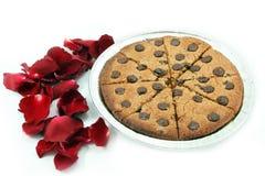 Gâteaux aux pépites de chocolat mous avec des pétales de rose sur le fond blanc Image libre de droits