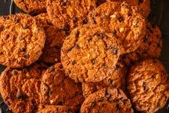 Gâteaux aux pépites de chocolat sur le fond rustique de noir foncé empilé images libres de droits