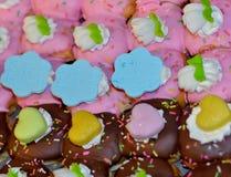 Gâteaux couverts du chocolat, givrage rose avec de la crème blanche Photo stock