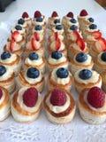 Gâteaux crèmes avec les baies rouges image libre de droits