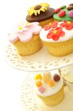 Gâteaux décorés de tasse sur le support de gâteau Photographie stock libre de droits