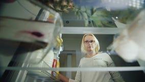 Gâteaux délicieux dans le réfrigérateur Une jeune femme ouvre la porte de réfrigérateur et prend un plat avec un gâteau Nourritur banque de vidéos