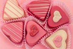Gâteaux en forme de coeur roses de petits fours vus d'en haut décoré autour des lettres roses énonçant l'amour Photos libres de droits