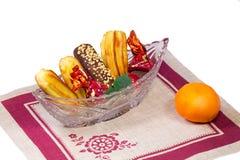 Gâteaux et bonbons dans un vase en cristal, une mandarine, une serviette sur W Photos libres de droits