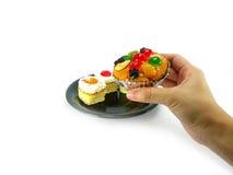 Gâteaux et main sur le fond blanc Photo libre de droits