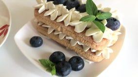 Gâteaux faits de biscuits et crème de savoiardi Décoré des myrtilles et de la menthe Mensonge des plats banque de vidéos