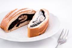 Gâteaux savoureux de petit pain de cacao arrosés avec du sucre d'un plat avec une fourchette, d'isolement sur le fond blanc Images libres de droits