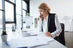 Gähnende Geschäftsfrau am Arbeitsplatz Stockbilder