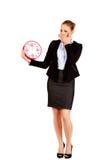 Gähnende Geschäftsfrau, die Bürouhr hält Stockfoto