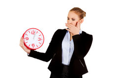 Gähnende Geschäftsfrau, die Bürouhr hält Stockbild
