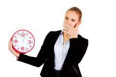 Gähnende Geschäftsfrau, die Bürouhr hält Lizenzfreies Stockbild