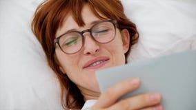 Gähnendes Lügen des Mädchens auf dem Bett mit einem Buch Abschluss oben stock footage