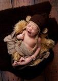 Gähnendes neugeborenes Baby, das einen Affe-Hut trägt Stockbilder