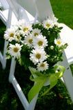 Gänseblümchen-Blumenstrauß auf Hochzeits-Gast-Stuhl Stockfotografie